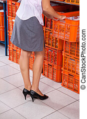 Woman Pulling Basket From Stack