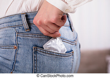 Woman Pulling Out Condom From Her Jeans Pocket