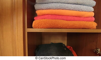 Woman pulling out fluffy bath towel from the shelf of...