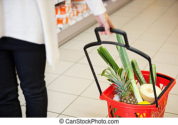 Woman pulling Shopping Basket in Grocery Store