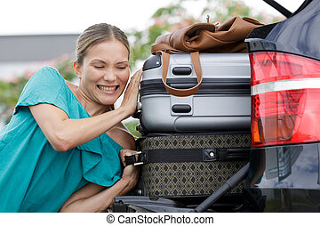 woman pulling suitcase out of trunk