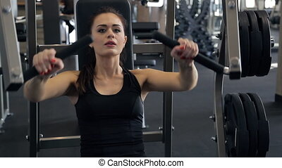 Woman pumping chest muscles on special equipment in sport gym
