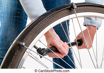 Woman pumping on a bicycle wheel - studio shoot
