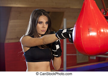Woman punching bag in gloves