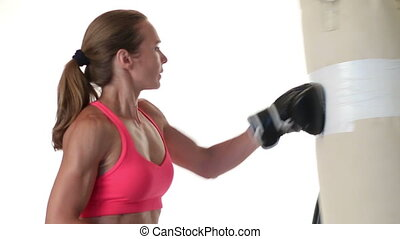 Woman Punching Heavybag - Woman working out with a heavybag....
