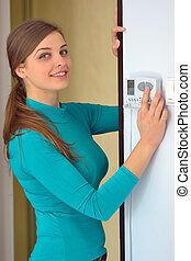 woman push button digital thermostat at house