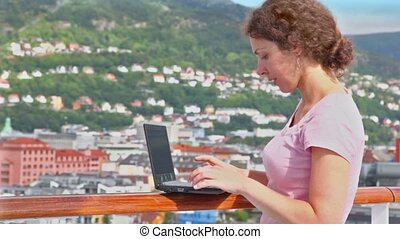 Woman pushes buttons on netbook at deck of ship in port...
