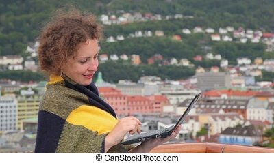 Woman pushes buttons on netbook at deck of ship in port