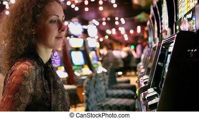 Woman pushes buttons on play machine in casino and becomes very happy when wins