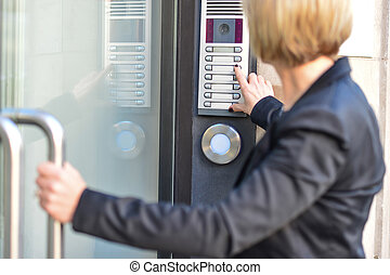 Woman pushing a intercom button