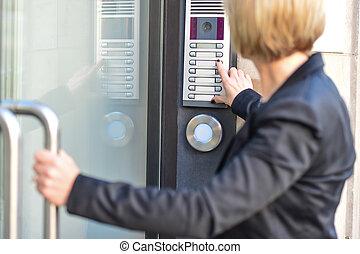 Woman pushing a intercom button
