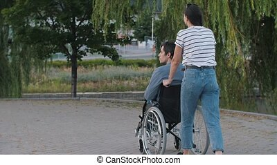 Woman pushing a man in a wheelchair at the park