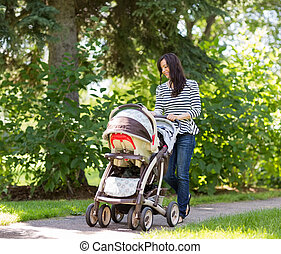 Woman Pushing Baby Carriage In Park - Happy young woman...