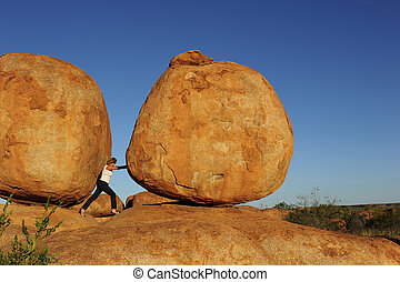 Sexy high heel woman pushing a huge boulder in sisyphus attempt, shot in remote outback Australia, with Devil's Marbles as spectacular landscape background and blue sky as copy space.