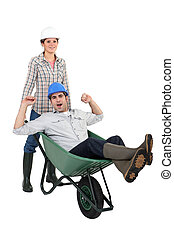 Woman pushing her colleague in a wheelbarrow