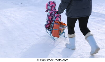 Woman pushing sled with small girl in winter