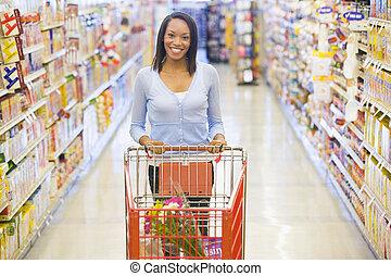 Woman pushing trolley in supermarket - Woman pushing trolley...