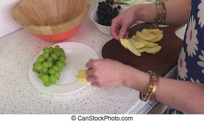 Woman put apple cloves on plate