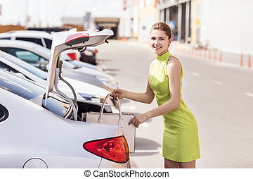 Woman put bag in the car trunk.