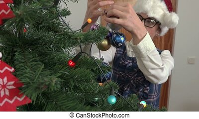 Woman put Christmas decorations on spruce