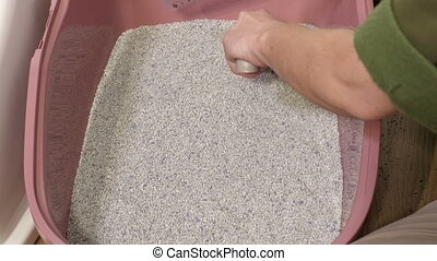 Woman put clay sand in cat litter box