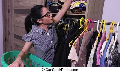 Woman put clothes in wardrobe