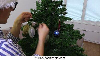 Woman put decorations on Christmas tree