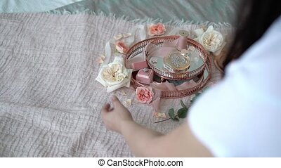 Woman put flowers at pink tray with bridal earrings proposal...
