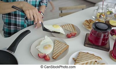 Woman put fried eggs on plaete with toast. Woman set the table for breakfast