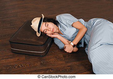 Woman put her head on suitcase and sleeps.