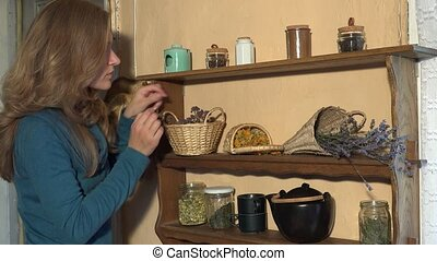 woman put in cup mint thyme herbal from shelves in kitchen. 4K