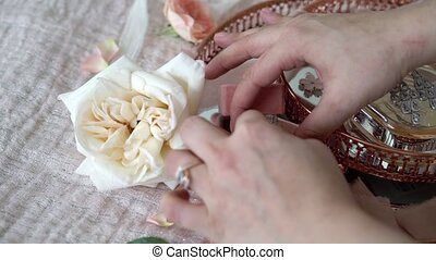 Woman put jewelry ring in a box at pink tray with bridal...