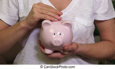 Woman put money banknote in piggy bank