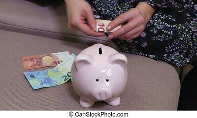 Woman put money in pink piggy bank