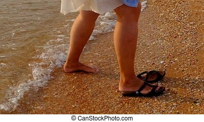 Woman put on slippers and walking on beach sunset steadicam...