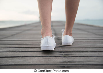 Woman put on white canvas shoes