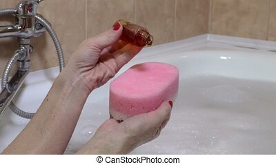 Woman put shampoo on sponge