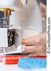 Woman put thread in sewing-machine