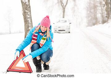 Woman put warning triangle car breakdown winter - Woman...