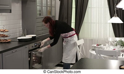 Woman puts a dish with the meat in the oven