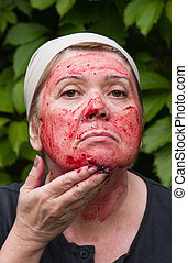 Woman puts a mask on the face of gooseberry