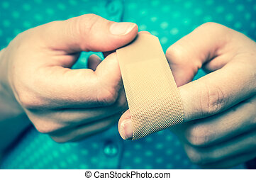 Woman puts a plaster on her injured finger