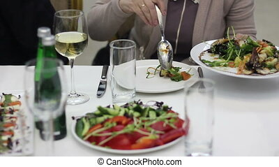Woman puts a salad to her plate