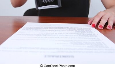 Woman puts a stamp on a contract thereby approving of this...