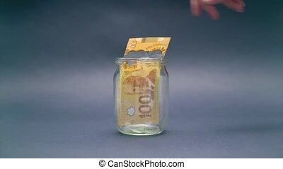 Woman Puts Canada Dollar 100 into a Glass Jar