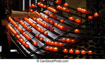 Woman Puts Candle in the Christian Church. Many Candles Are...