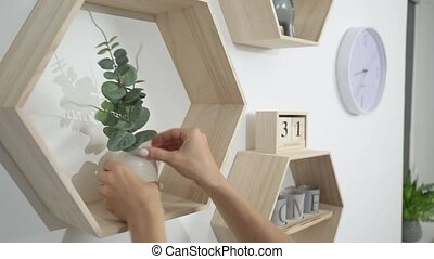 woman puts decor and flowers on the shelves on the wall -...