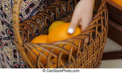 Woman Puts Fruits at Basket
