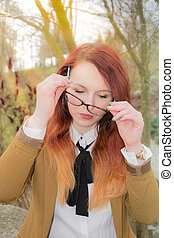 Woman puts glasses on - A young woman is wearing glasses ...