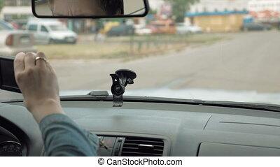 Woman puts GPS navigator on the car windshield